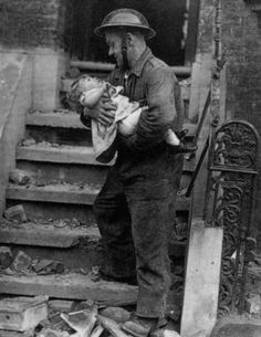 A rescue worker comforting a very small child amid air raid damage