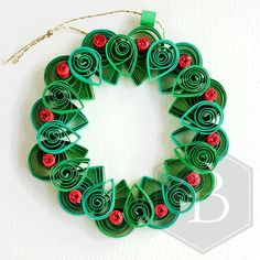 Add a touch of sparkle to your home this Christmas with this striking quilled holly wreath Christmas decoration. It can be hung on a Christmas