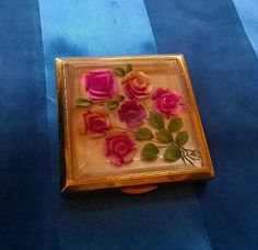 A wonderful old 1950s powder compact with reverse painted roses under lucite. Beautifully made and in very good condition. Engraved with the name Denise. The compact is made by Melissa. It has a well designed mechanism for keeping your powder behind a door so it doesnt mess up