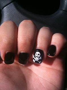 black nail polish with a skull ring finger