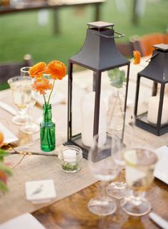 I like the idea of this for a centerpiece.  Neat lantern, small vase of flowers, candle, and table number?