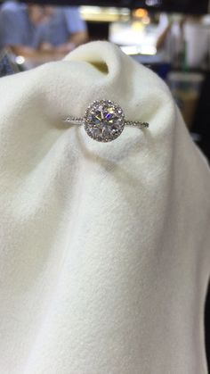 Classy circle halo engagement ring with round brilliant cut diamond center stone and side diamonds