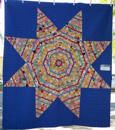 This first quilt is a stunning example of string piecing. Each large diamond is made up of 64 smaller string pieced diamonds. That is 272 total string pieced diamonds! If you look closer you will see that the quiltmaker put a solid colored scrap in the center of each diamond and when she pieced the diamonds together alternated those colors so you can see a ring of red, or green, or cheddar, or blue. This quilt was part of the antique trunk show and is owned by Jeananne Wright