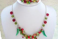 Štipľavý náhrdelník; základ ktoréh tvorí Chilli prívesky z mačacieho oka (imitácia pravého minerálu)  v červenom a zelenom odtieni, brúsené sklo (ohňovky), rôzne tvarovky a iné korálky ....  Hodinky v sviežom červeno-zelenom odtieni :).  Nájsť si tam môžte voskované perly v sýtom červeno odtieni, žíhané zeleno-červené lístky, a ďalšie rôzne tvarové korálky :).