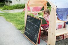 An example of Waldorf playhouse encouraging imaginative play.  This child seems to be using it as a curbside store!  Awesome!  I want one of these!