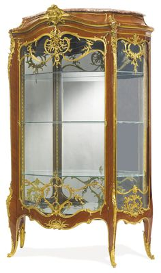 FRANÇOIS LINKE 1855 - 1946 A GILT BRONZE MOUNTED KINGWOOD VENEERED VITRINE PARIS, EARLY 20TH CENTURY, INDEX NUMBER 905, THE MOUNTS DESIGNED BY LÉON MESSAGÉ surmounted by a Serraveza marble top, the cresting centered by a female mask, opening to a mirrored interior and three glass shelves height 6 ft. 2 1/2 in.; width 4 ft.; depth 21 1/2 in. 189 cm; 122 cm; 54.5 cm