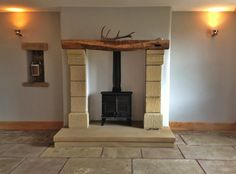 sandstone fireplace with wood burner and reclaimed oak mantel