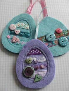 Delicados huevos de Pascua para guindar, hechos de fieltro y decorados con botones y cintas de formas y tamaños diferentes.