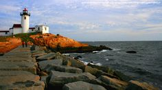 Ocean and Lighthouse, Stone Boulder Walkway, White Lighthouse, Blue Sky and White Clouds, New England Seascape Digital Wallpaper Screensaver