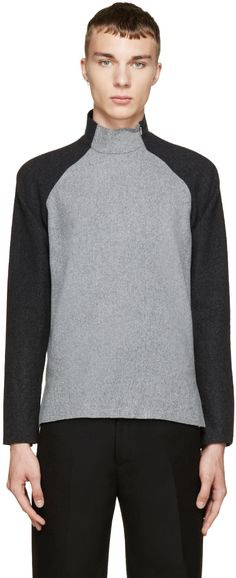 Long sleeve felted wool sweater colorblocked in tones of grey. Turtleneck collar. Raglan sleeves. Zippered closure at front armscye. Tennis tail hem. Tonal stitching.