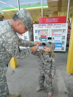 FAYETTEVILLE, N.C. --  Ellie, daughter of Army Staff Sgt. Tommy Rieman, a  Silver Star recipient with the Virginia National Guard, learns to salute  from Army Sgt. 1st Class David Nobles, North Carolina National Guard, at a NCNG community relations event with 'Support Our Troops', here Aug. 16.