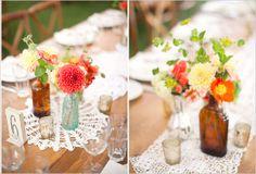brown bottles, bright flowers, doily runner