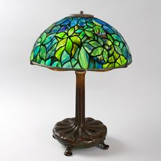 """Woodbine"" Tiffany Lamp A Tiffany Studios New York ""Woodbine"" leaded table lamp. The shade sits on a four footed patinated base. A dash number (-) designates a special order shade."