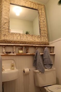 - salvaged wood rail turned into towel holder and shelf.  salvaged ceiling tins turned into a mirror -
