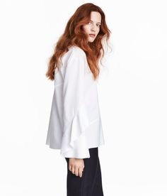 Check this out! CONSCIOUS EXCLUSIVE. Straight-cut blouse in textured-weave fabric made from silk and organic cotton. Long sleeves with flared cuffs with button - one sleeve with a wide flounce. Opening at back of neck with button, asymmetric seam at waist, and frayed edges. - Visit hm.com to see more.