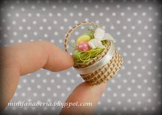 A Miniature Easter basket with Easter eggs and ecru ribbon with a little bow in one inch scale (1:12)