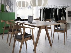 IKEA- A conference room with a long table in walnut veneer and chairs with leather seat, green cabinets