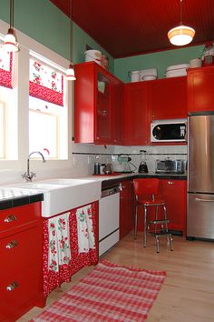 love a red kitchen. great color on the walls, too.