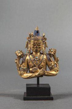 Torse de Vajradara, tenant la ghanta et le vajra dans ses mains croisées sur sa poitrine d'ou s'échappe deux branches de lotus épanouies. Bronze doré au mercure incrusté de turquoises à rehaut de pigments bleus. Chine. Tibet. 16 ème siècle. 8,5 x 7,5 cm