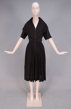 CLAIRE McCARDELL CRINKLED COTTON DAY DRESS, 1940's. Black gauze with short sleeve cape collar, contoured waist and full skirt having fourteen brass hook and eye closures.