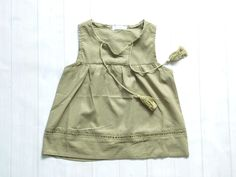 Light+and+airy+khaki+green+sleeveless+peasant+top+with+tassels+dangling+in+front.+Along+the+bottom+is+a+see+through+trim.+The+neckline+ha…