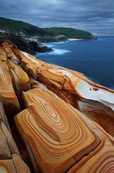 Lliesegang rings in sandstone, Bouddi National Park, NSW, Australia. The sandstone cliffs are textured with liesegang rings — a geological phenomenon which creates coloured bands of cement found in sedimentary rocks and cut-across bedding.
