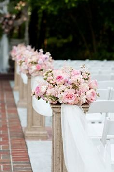 arrangements on pillars lining the aisle