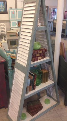 $350 This A frame bookcase was hand built using vintage house shutters. Its finished in a grayish green/ creamy white combo. Dimensions: H 64 x W