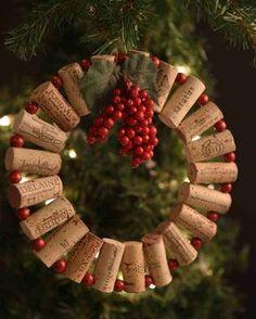 Ghirlanda fai da te di Natale con tappi di sughero, palline rosse e grappolo di bacche con foglie di agrifoglio.