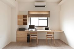 This truly minimalist home office design centers completely on a large light natural wood desk and storage set running the width of the wall. A singular window adds natural light to the bright space.