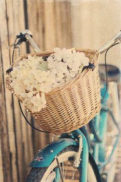 Basket full of white flowers on a blue bike