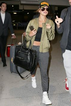 Hailey Baldwin wearing Saint Laurent Aviator Sunglasses, Pirello Podium Hat, Saint Laurent Court Classic Sneakers and Topshop Morris Ma 1 Bomber Jacket in Olive