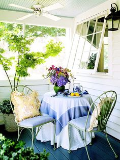 Simple Dining  Set a sweet table on a porch or patio -- no dining set needed. Simply drape a quilt, sheet, or blanket over a small round table and add two similarly sized chairs outfitted with a pair of throw pillows.