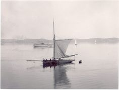 Sailboat in still water, on Gullmarn fjord outside Lysekil, Sweden. Skaftö island on the other side of the water. c. 1890