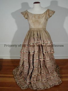 Ladies' full length straw-colored dress of a very thin, almost transparent gauze-like material with pink bands and flower-embroidered designs. 1855-1860. Gunn Memorial Museum