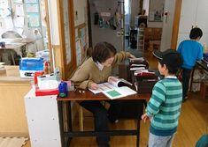 ルポ190222:子どもと話しながら連絡帳を開く中村真理子施設長。おやつの注文や配布物の準備、配慮が必要な子に関する情報共有は午前中に済ませる=東京都多摩市の貝取学童クラブで2019年1月28日午後3時半、大和田香織撮影