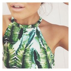 This palm printed halter top features the jungle-ly green print, exposed shoulders, and high neck 90s trends.