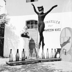 Seventeen-year-old Bianca Passarge of Hamburg dresses up as a cat and dances on wine bottles in June 1958. Her performance was based on a dream. She practiced for eight hours a day to do this.
