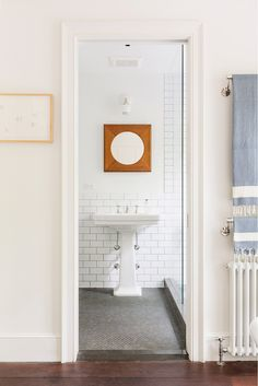 All-white bathroom with subway tile and wood mirror above sink