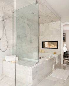 The shared wall between a master suite and the master bath is another great place for a dual fireplace. This bath was designed by none other than The Property Brothers. This page has some very useful information about home design and decor. Dream Bathrooms, Beautiful Bathrooms, Modern Bathroom, Modern Bathtub, White Bathroom, Master Suite Bathroom, Small Bathrooms, Paint Bathroom, Zen Bathroom