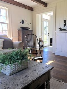 bright + inviting primitive living room... loving the wood textures and whites and natural greenery