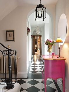 Love the black and white floors with the pink chest, rounded doorways and windows, elegant stairway.  entryway.  home decor and interior decorating ideas.