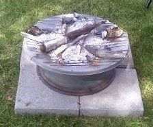 Fire pit from an old satellite dish, a truck rim a refrigerator rack and some wire mesh.
