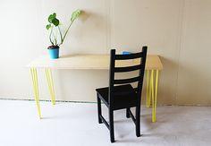 en smalle bordplade med gule bordben
