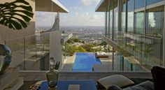 Aviici's insane mansion in the Hollywood Hills has a stucco facade, stone pavers, linear pools, a flat roof, walls of glass, unique artwork, and an amazing view of the city below.