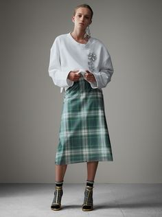 An A-line skirt in a tactile mix of soft-touch plastic and silk. Sitting high on the waist, it has a glossy tartan-printed front. Style with sandals and socks for a sense of undone elegance.