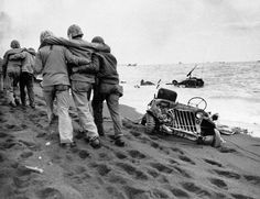 Striking images from the battle of Iwo Jima:The going is hard in the volcanic sand as wounded Marines are held by fellow Marines, less seriously wounded, and Navy medical corpsmen bound for an aid station. Around them is wrecked American equipment, on the beach and in the water