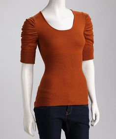 This chic sweater will keep any haute mama toasty warm. The ribbed design provides plenty of comfortable stretch while ruching and buttons decorate each sleeve.Measurements (size S): 26'' long from high point of shoulder to hem55% cotton / 45% acrylicMachine wash; tumble dryImported