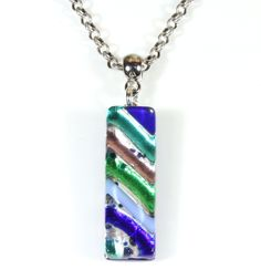 """""""Murano No.1"""" Murano Glass Pendant Necklace, 26 Inches Adjustable. A stunning authentic Murano (Venetian) fused glass pendant hangs from a high quality rolo chain in antique silver color. The pendant has bright stripes in shades of blue on a silver background; one photo shows the back stamped with the Murano Glass guarantee. Will look striking with your outfit! Falls at about chest level; comes in a nice white gift box with Style ARThouse logo. Made at Style-ARThouse in Maryland; comes…"""