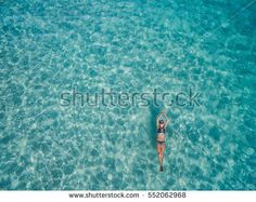 Aerial view of young woman in bright bikini is swimming in the transparent, blue sea. Top view of slim woman floating on the water of Andaman sea. Khai Nok island, Phuket, Thailand.